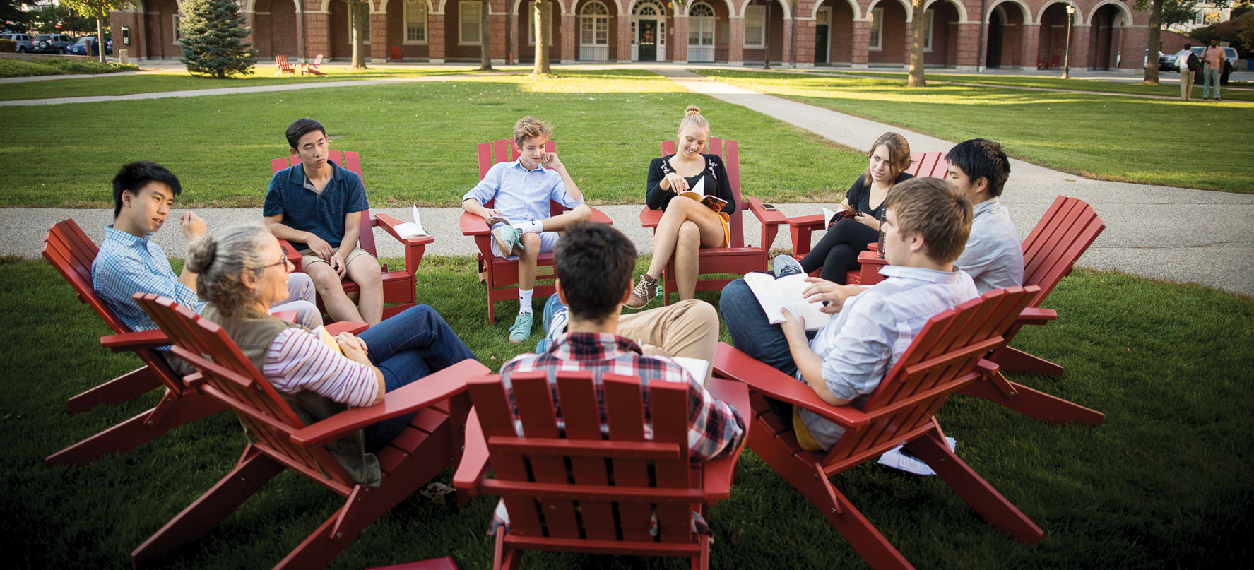 Phillips Exeter Academy students sitting in Adirondack chairs on the quad.