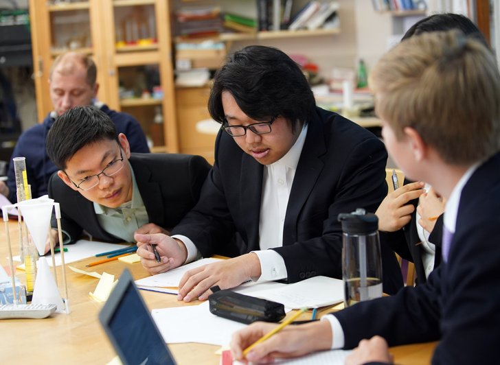 Exeter students confer during a physics competition at Exeter.