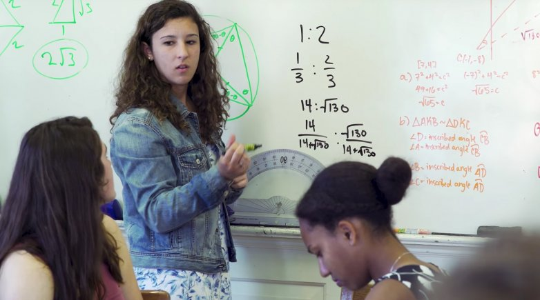 Student standing at the board presenting a math problem to students seated at the Harkness table.