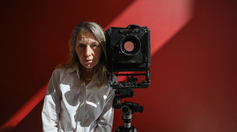 Cheryle St. Onge standing next to a camera.