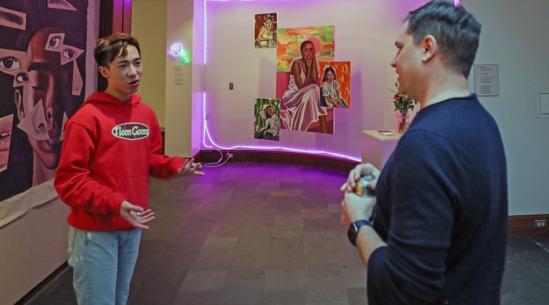 Justin Li and M. Sharkey discuss Li's artwork in the foyer of the Lamont Gallery.