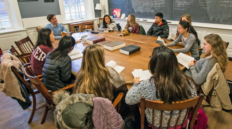 Exeter students and teacher seated around a Harkness table.